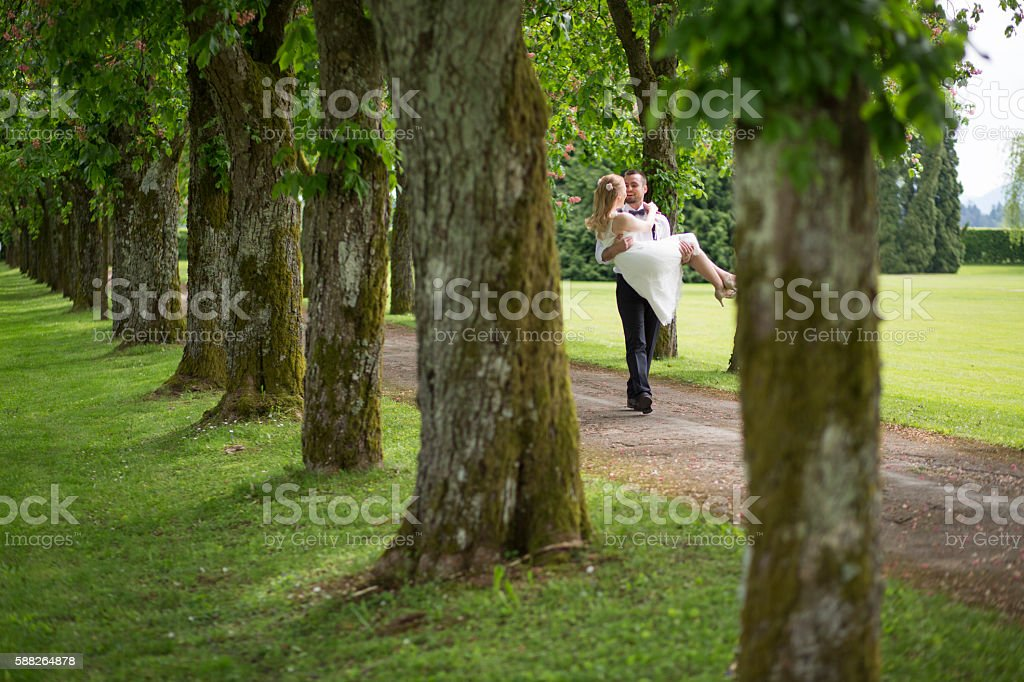 Groom carrying his bride and walking stock photo