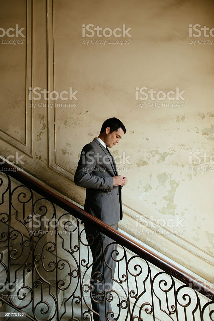Groom fixing his suit on a stairway stock photo