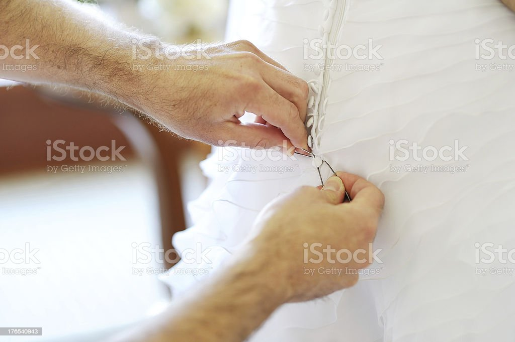 Groom helping bride to put  wedding dress on royalty-free stock photo