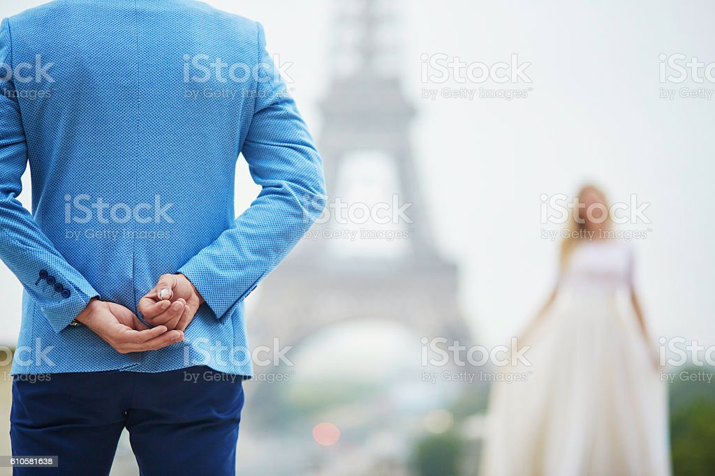 Groom hiding the wedding ring behind his back stock photo
