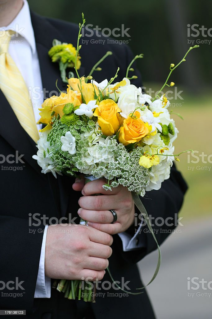 groom holding a bouquet stock photo