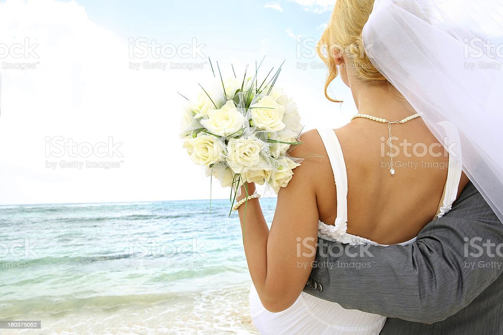 Groom holding his bride by the ocean stock photo