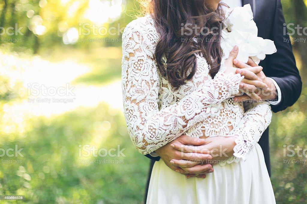 Groom hugging his bride stock photo