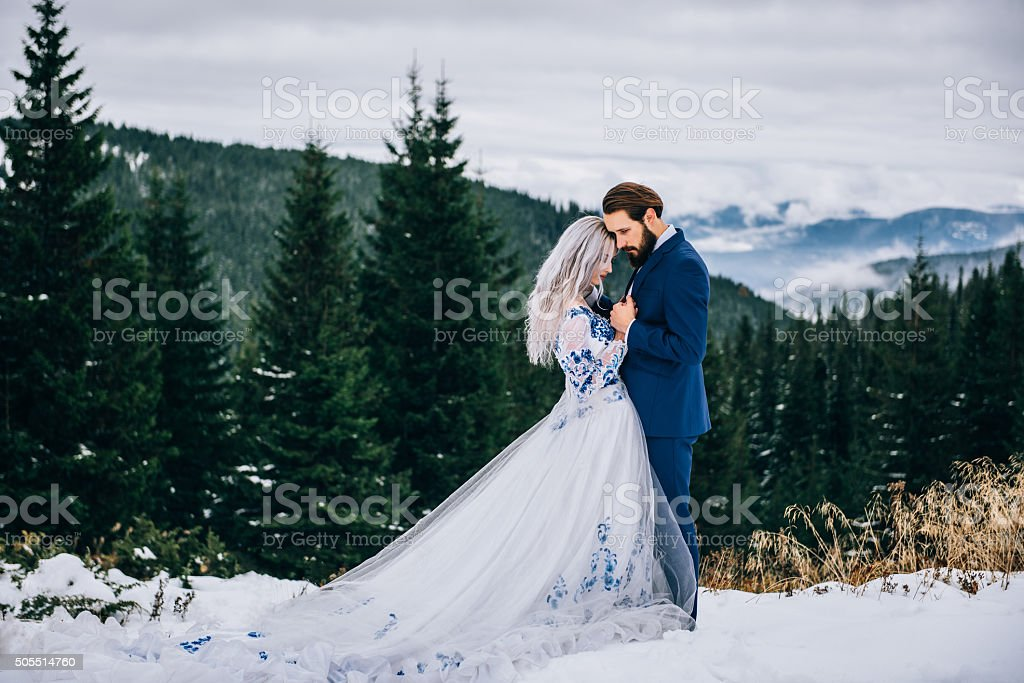 groom in a blue suit and bride in white stock photo