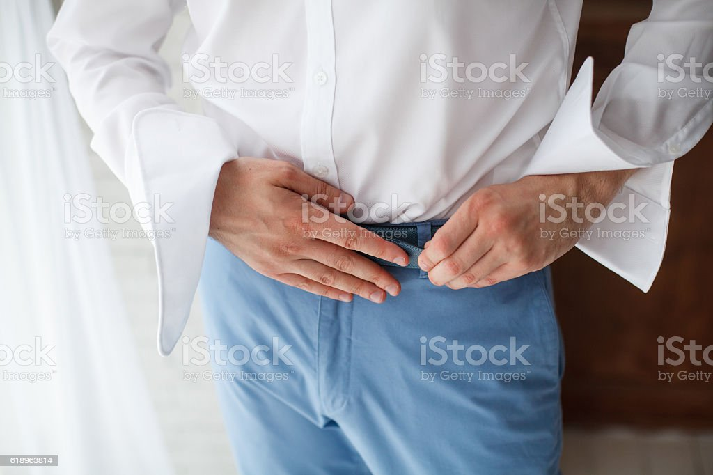 Groom in shirt holding hands on the belt, wedding suit stock photo