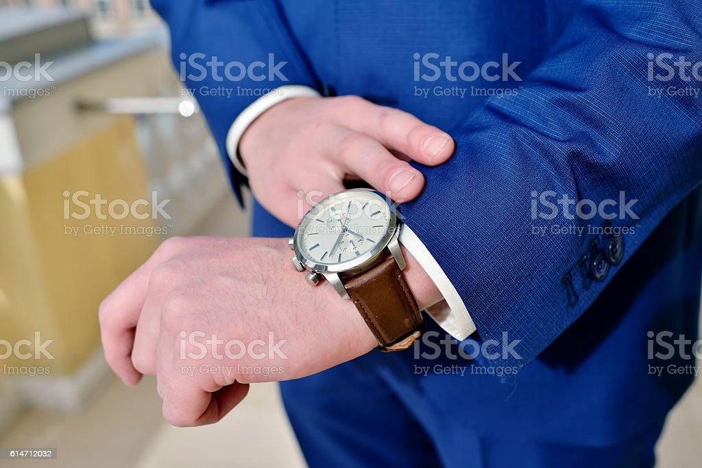 Groom is wearing a wrist watch indoors stock photo