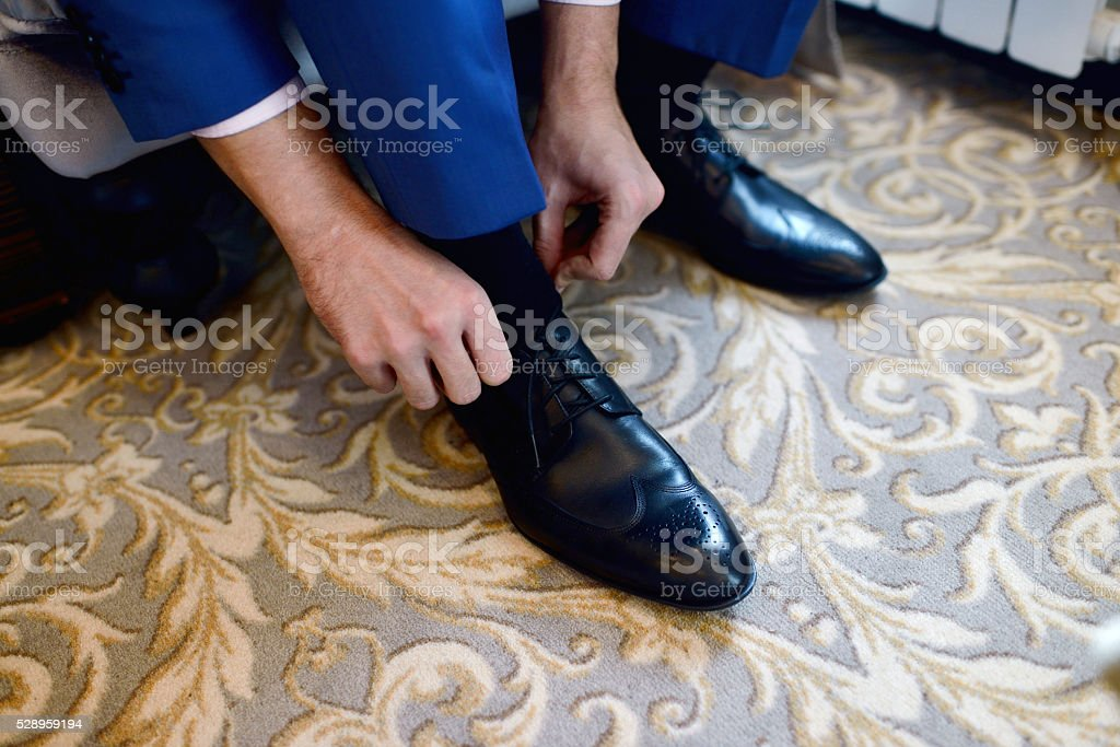 Groom is wearing shoes indoors. Male portrait of handsome guy stock photo