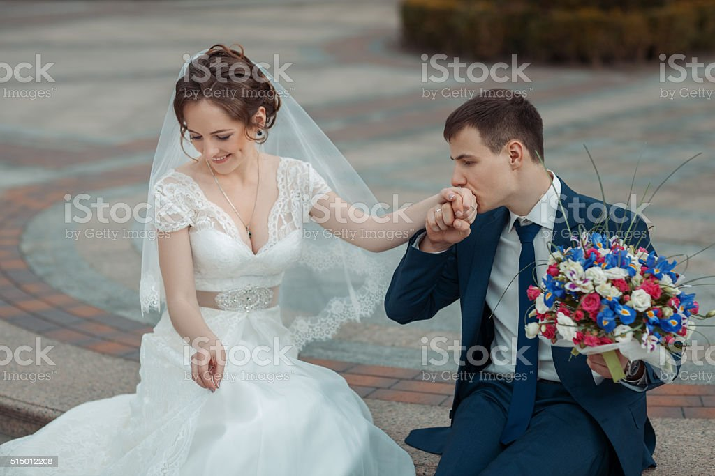 Groom kisses the hand of  bride stock photo