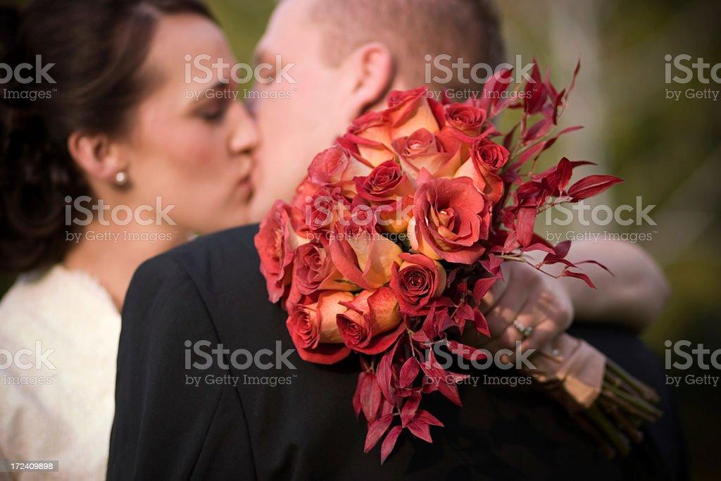 Bräutigam Küssen Braut Holding roten Rose Bouquet – Foto