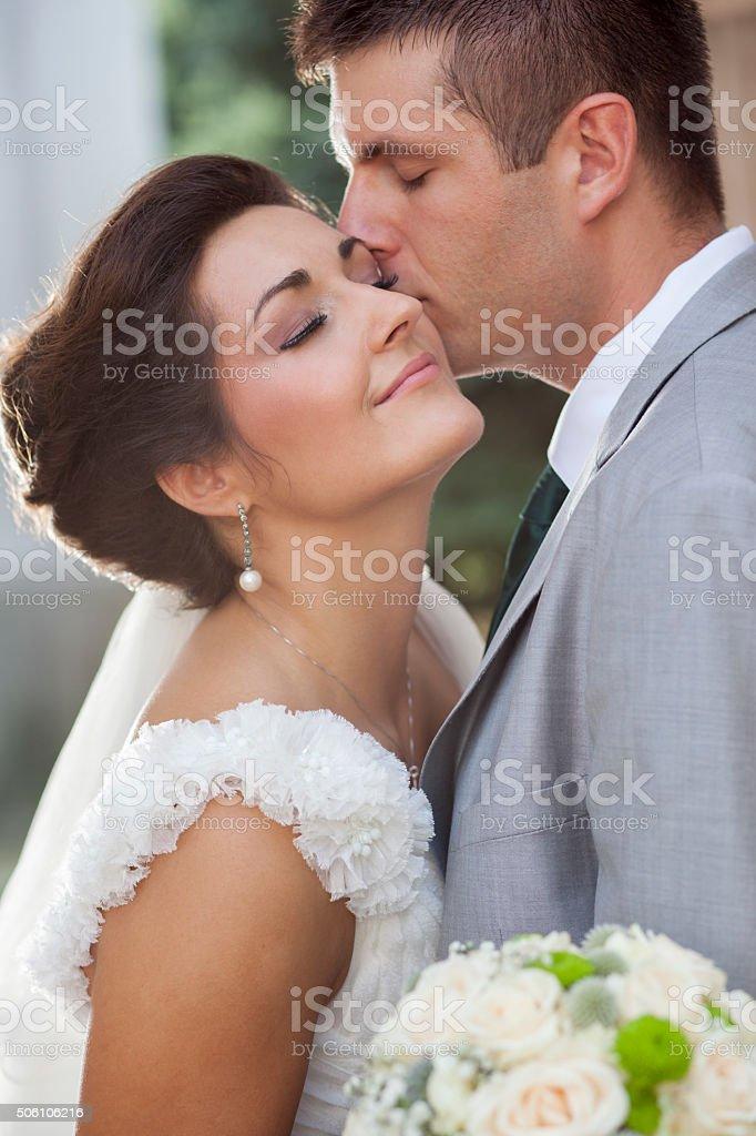 Groom kissing the bride stock photo