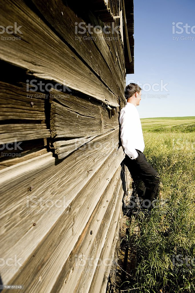 Groom Leaning Against Wall of barn stock photo