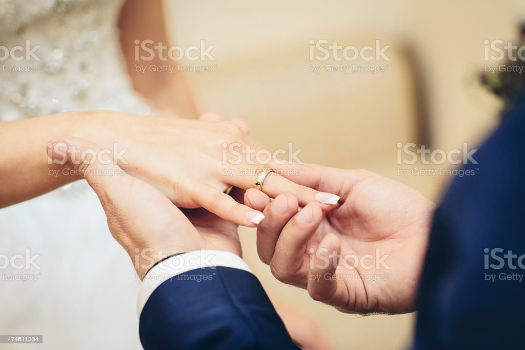 groom placing an engagement ring stock photo