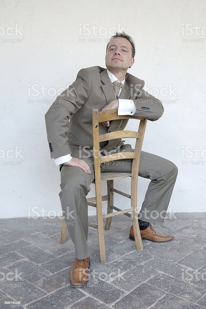 Groom posing on a chair against a white backdrop royalty-free stock photo