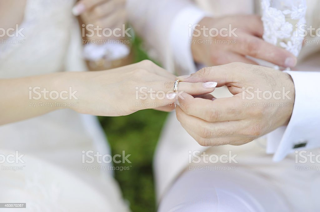 Groom putting a ring on bride's finger royalty-free stock photo