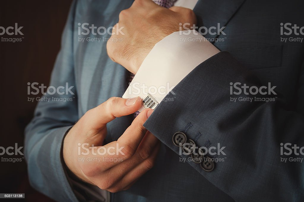 groom putting on cuff-links as he gets dressed stock photo