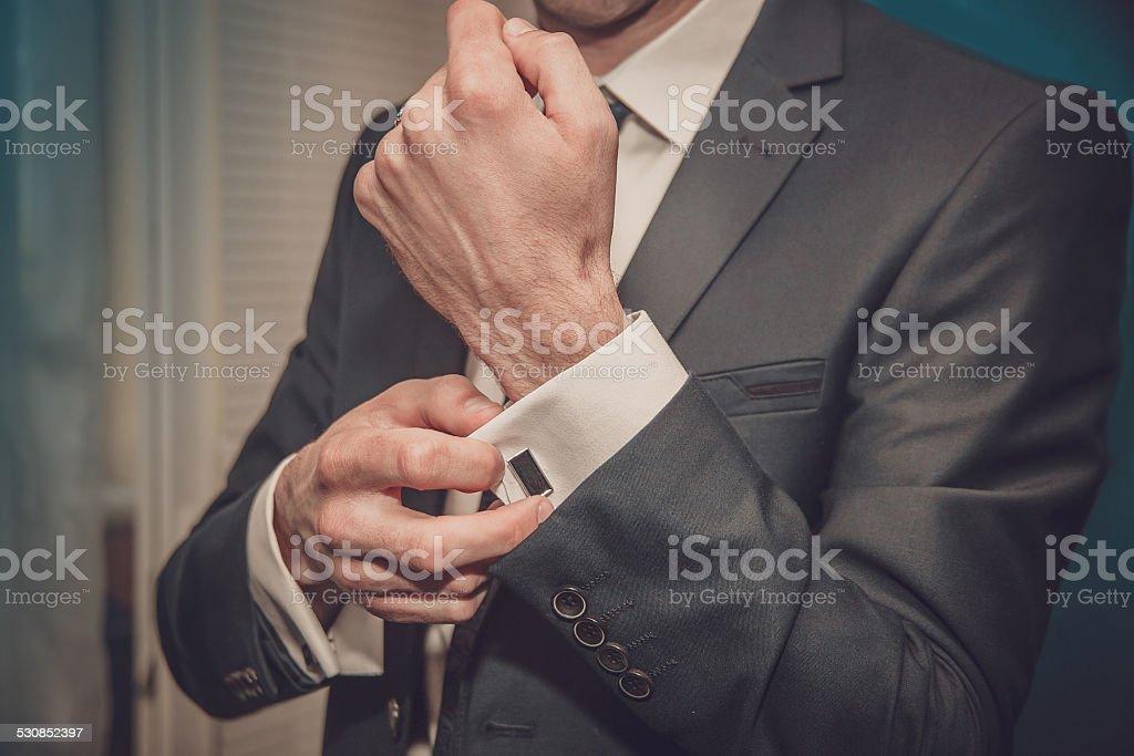groom putting on cuff-links stock photo