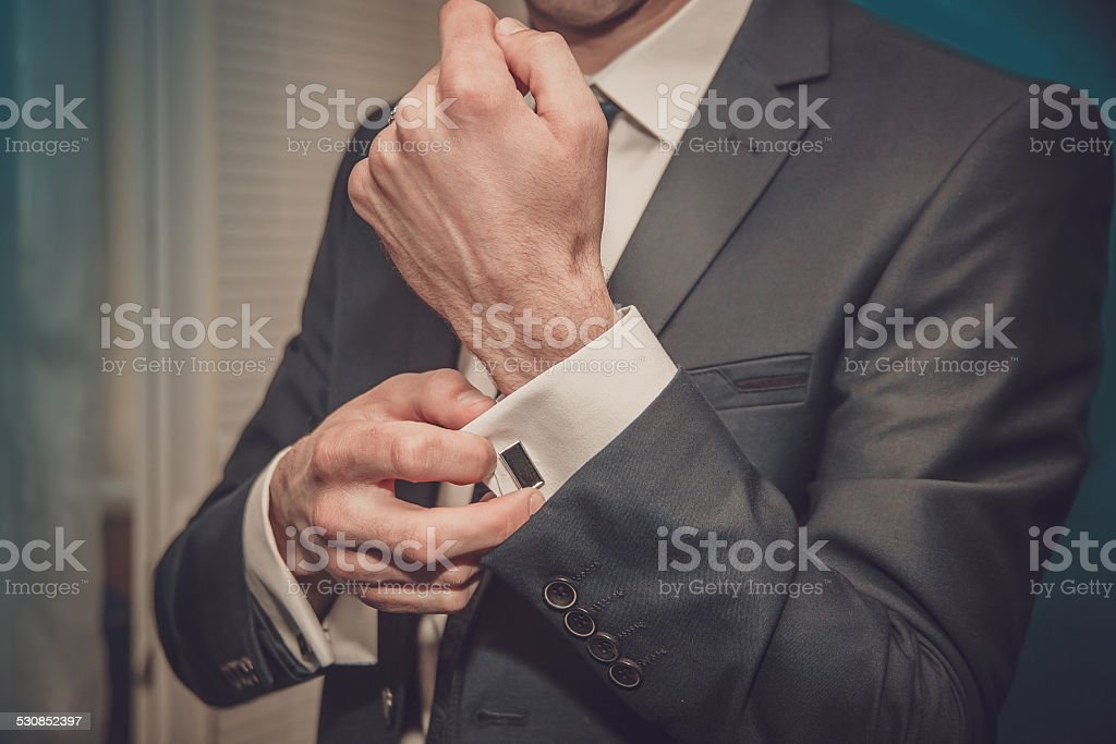 groom putting on cuff-links stock photo