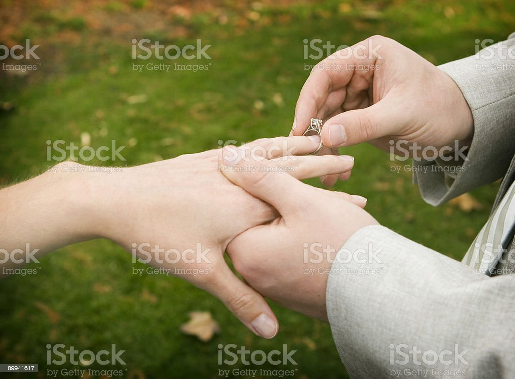 groom putting ring on bride royalty-free stock photo