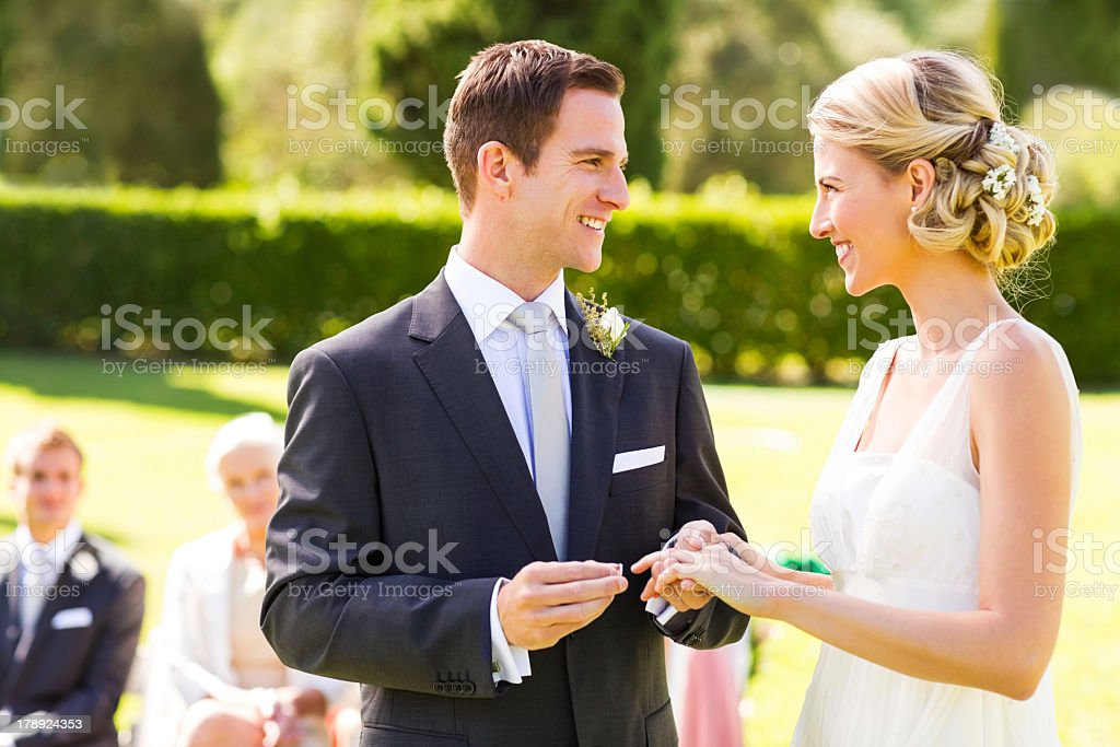 Groom Putting Ring On Bride's Finger stock photo