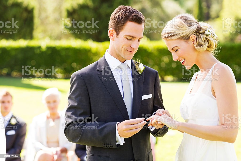 Groom Putting Wedding Ring On Bride's Finger During Ceremony stock photo