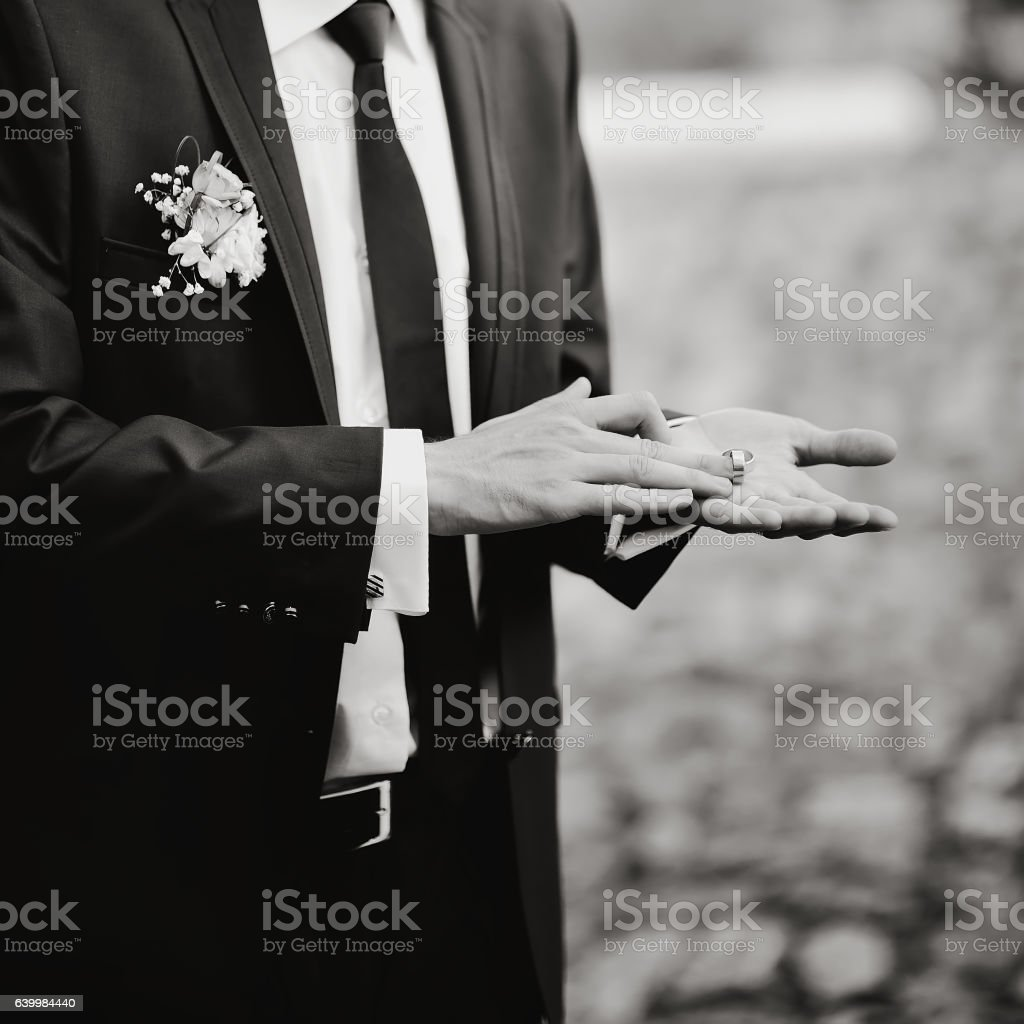 Groom showing two wedding rings on his palm stock photo