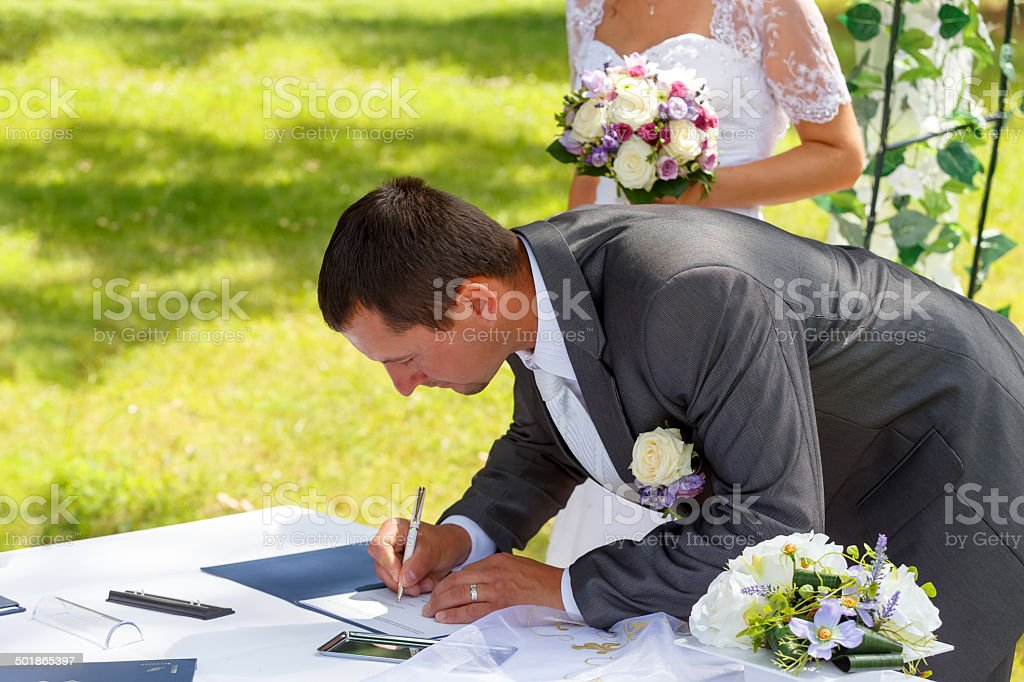 groom signing certificate in park stock photo