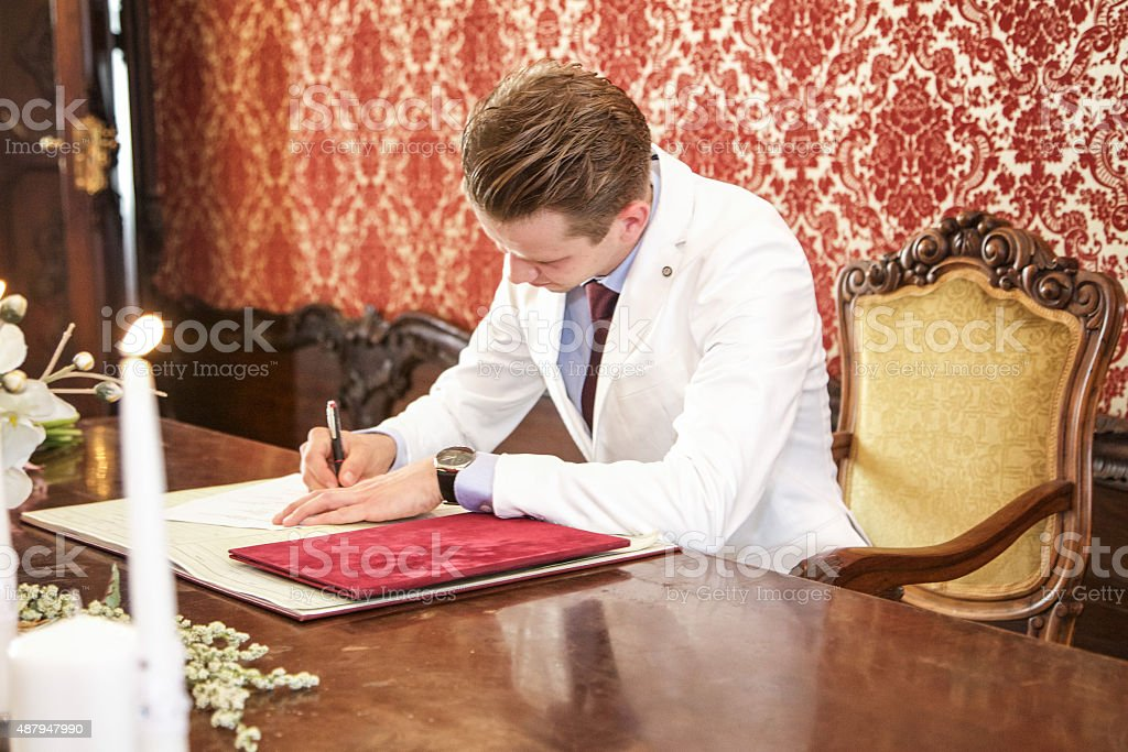 Groom signing the book stock photo