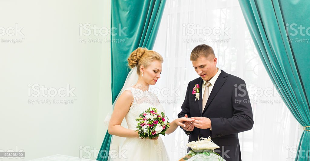Groom slipping ring on finger of bride at wedding stock photo