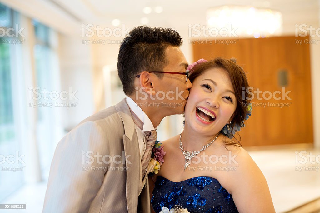 Groom to kiss the bride cheek stock photo