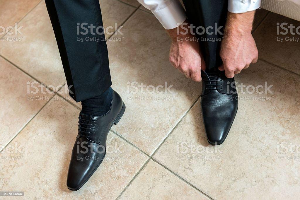 Groom tying his shoelace stock photo