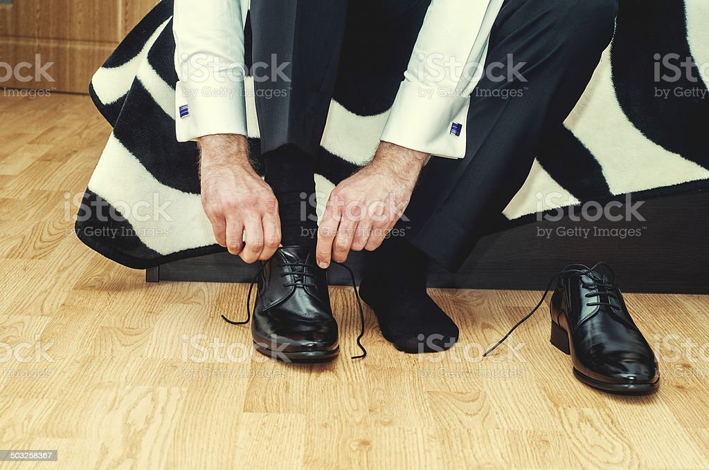Groom wearing shoes on wedding day, tying the laces stock photo