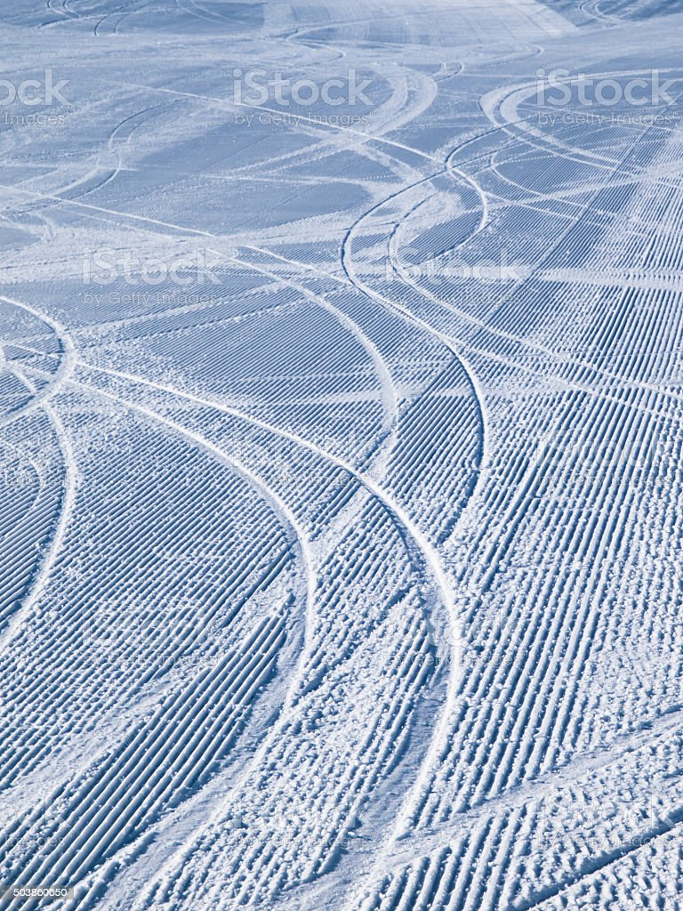 Groomed ski slope with several tracks stock photo