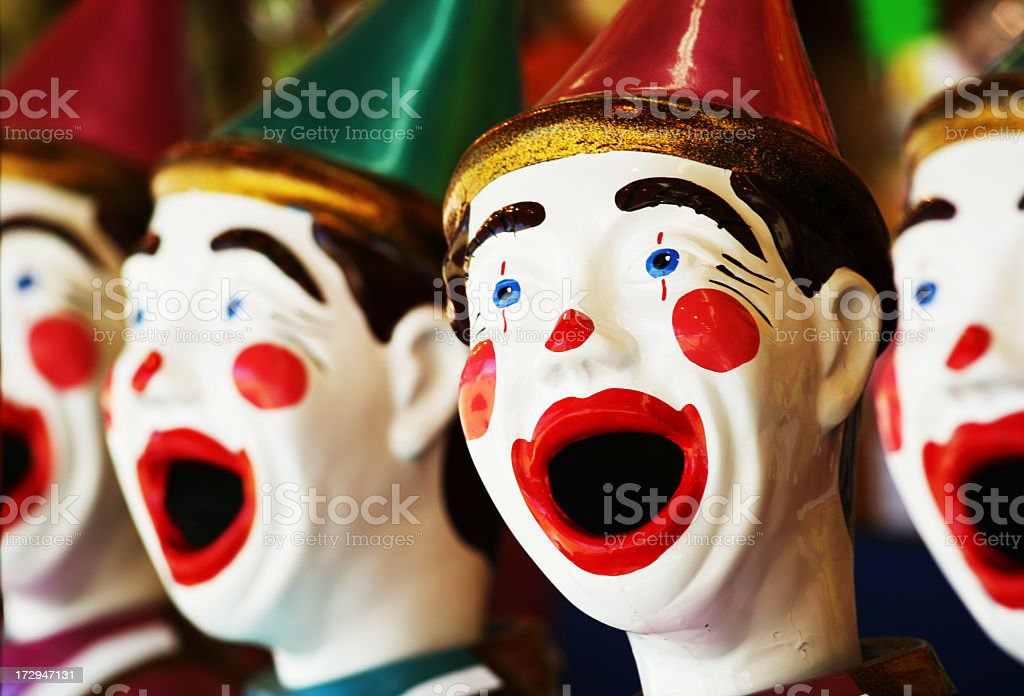 Grotesque gaudy moulded clown faces in a side show stock photo