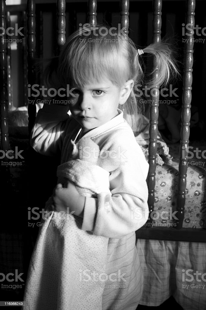 Grouchy Angry Toddler Holds Doll and Frowns beside Crib stock photo