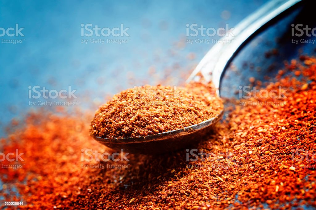 Ground chili pepper in a spoon on a dark background stock photo