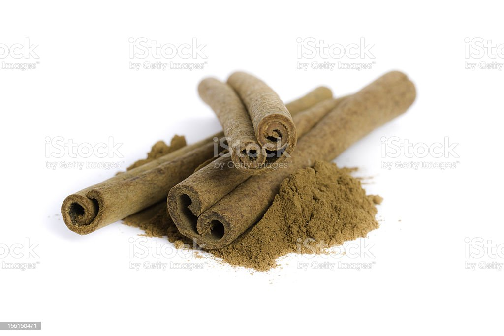 ground cinnamon and cinnamon sticks isolated on white stock photo