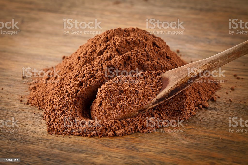 Ground cocoa heap on rustic wood table stock photo
