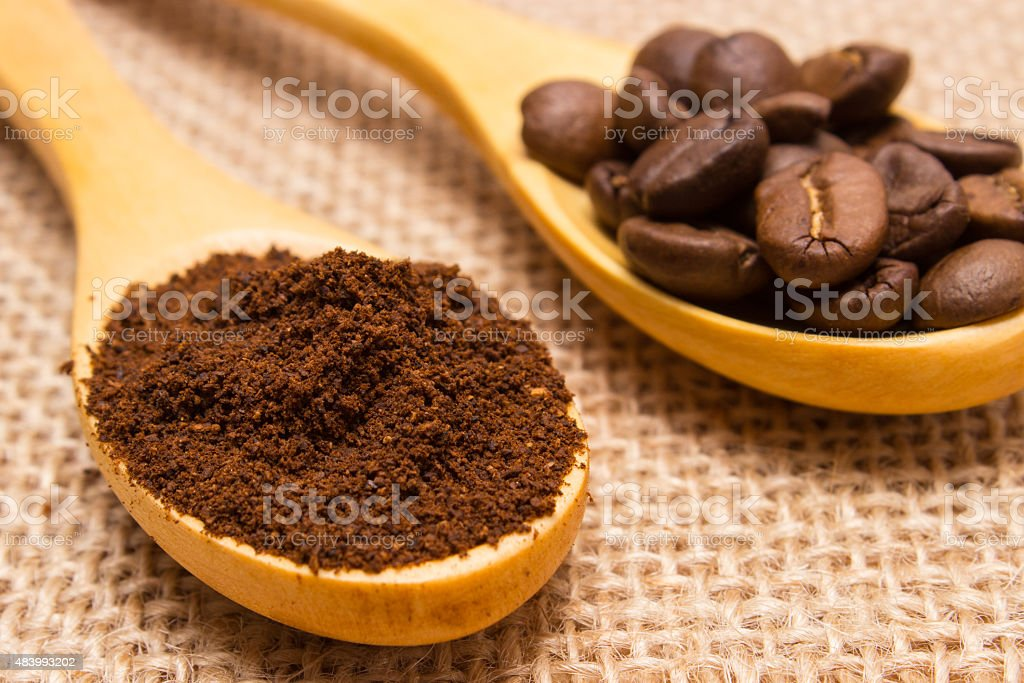 Ground coffee and grains with wooden spoon on jute canvas stock photo