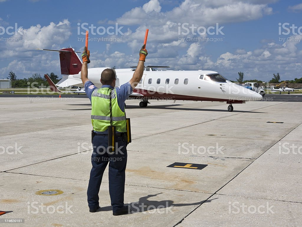 Ground Crew Guides Taxiing Private Jet Into Parking Spot stock photo