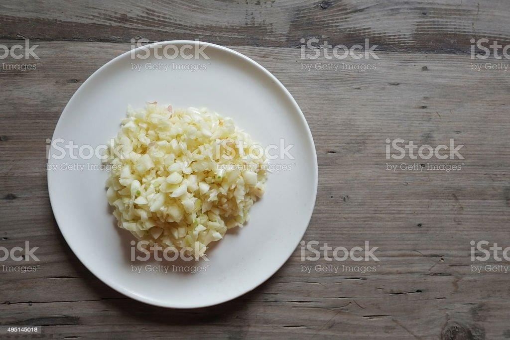 ground fresh garlic on white plate stock photo