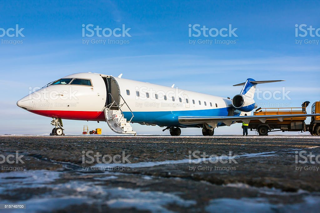 Ground handling of private airplane in a cold winter airport stock photo