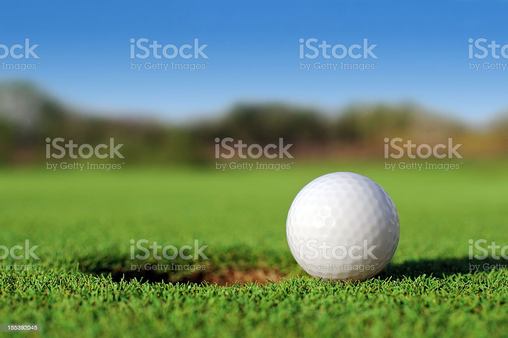 Ground level close up of golf ball close to hole stock photo