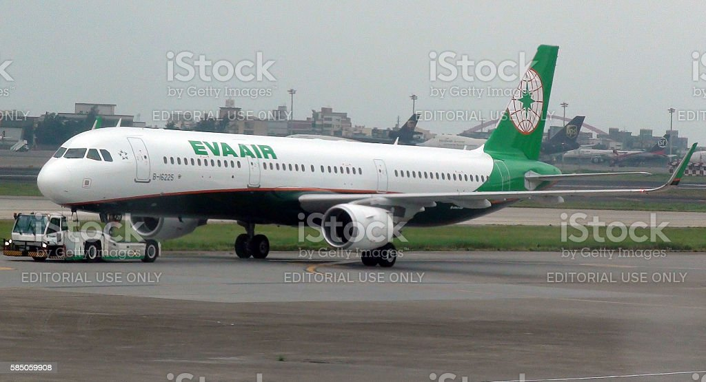 Ground Staff With Pushback Tractor Towing EVA Air To Runway stock photo