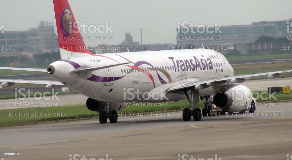 Ground Staff With Pushback Tractor Towing Transasia Airways To Runway stock photo