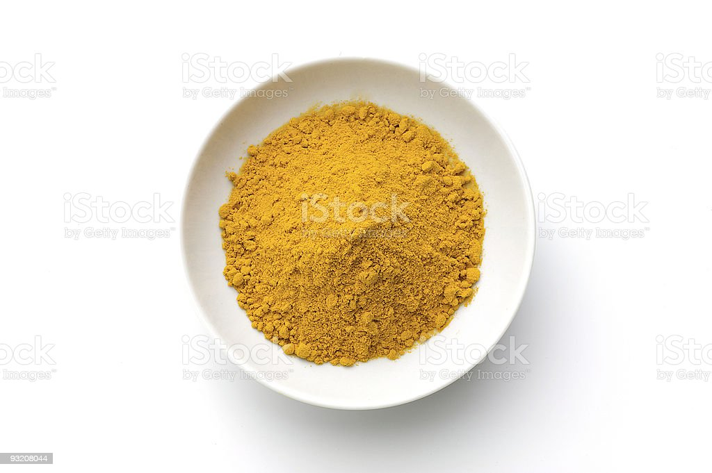 Ground turmeric powder in a white bowl on a white background royalty-free stock photo