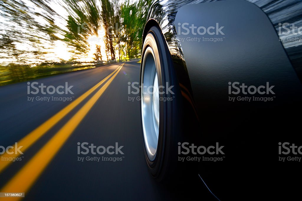 Ground view of car tire speeding along country road sunset stock photo