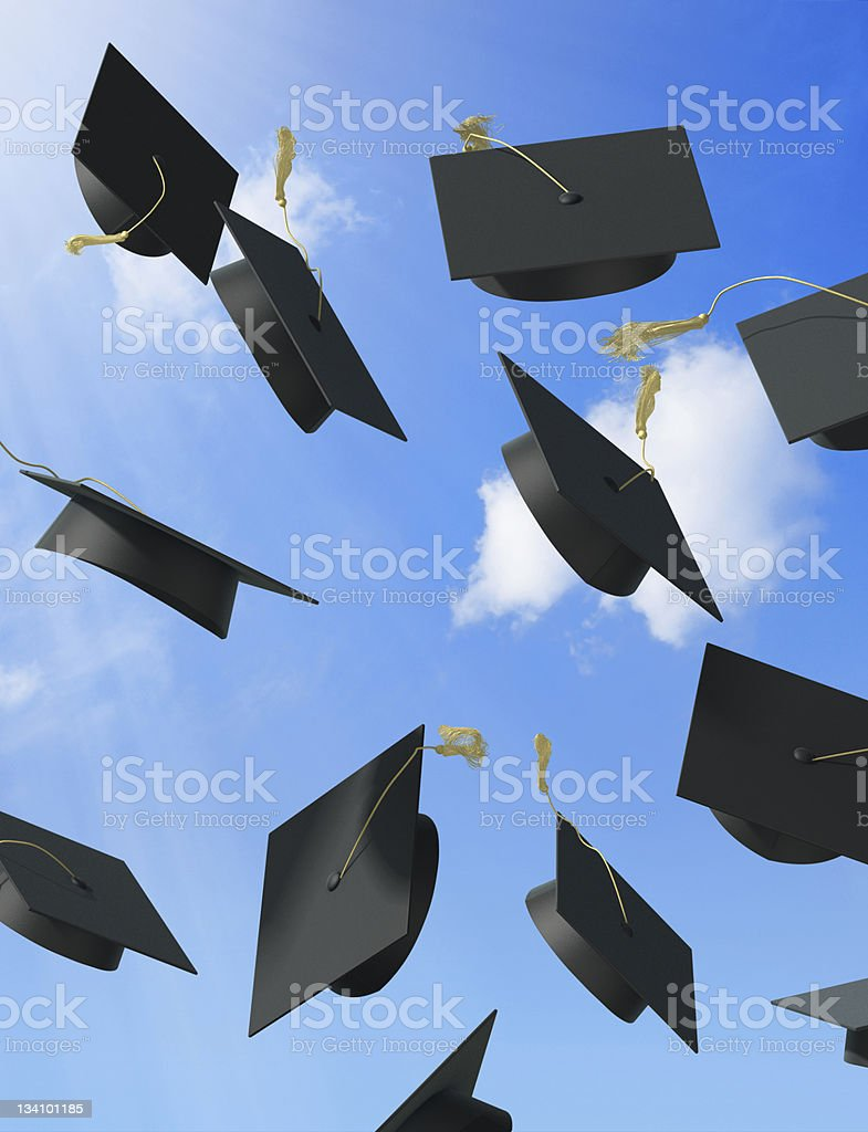 Ground view of graduation hats being thrown in the air stock photo