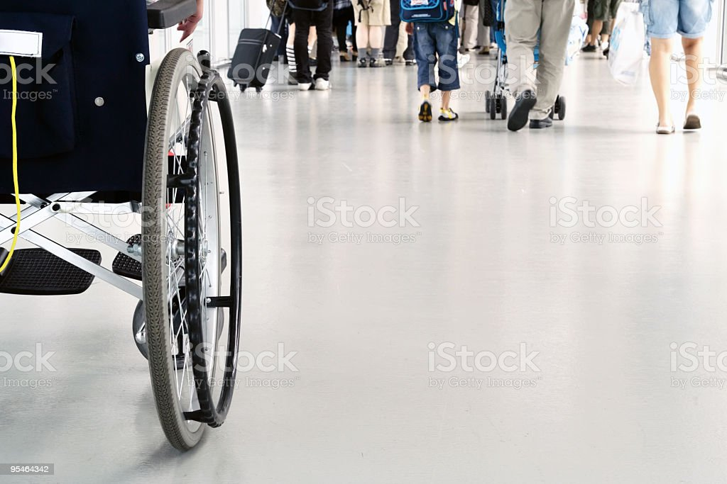 Ground view of the back of a wheelchair and people walking stock photo