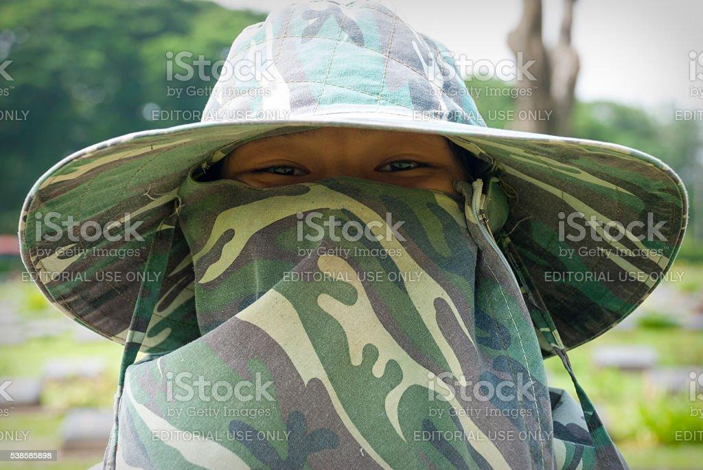 Groundskeeper at Kanchanaburi War Cemetery in Thailand stock photo