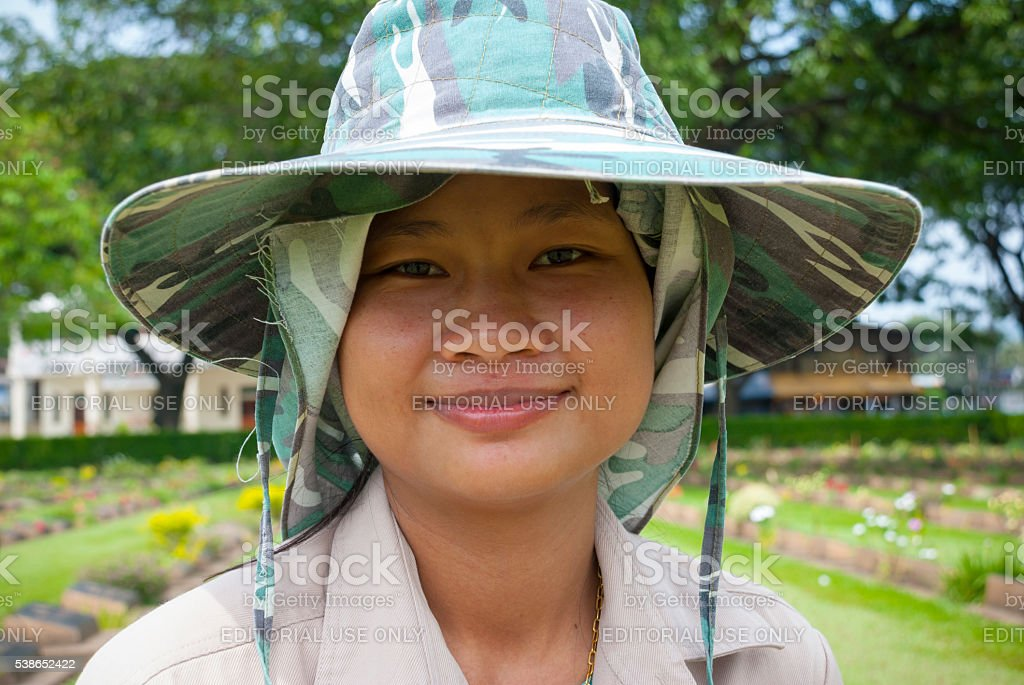 Groundskeeper at Kanchanaburi War Cemetery in Thailand stock photo